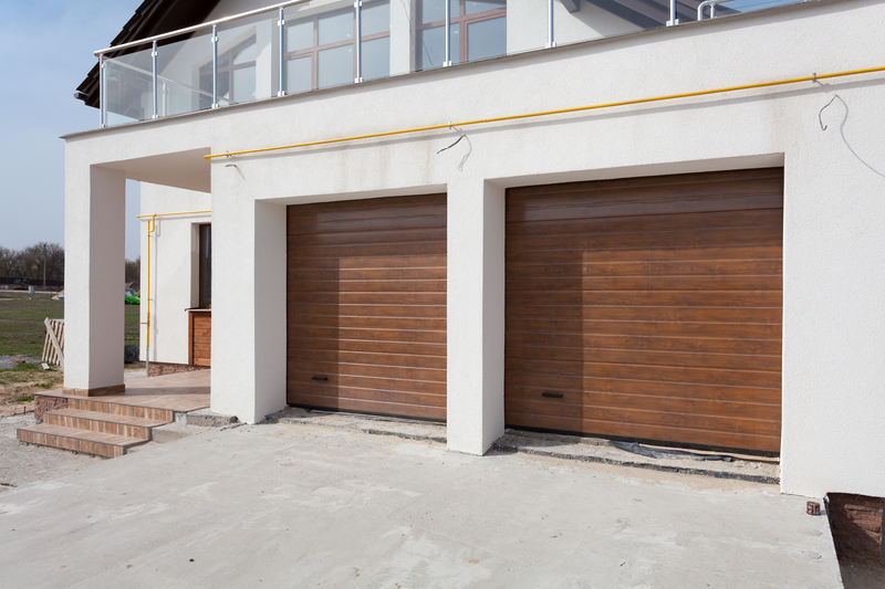 two wooden up and over garage doors on a new build